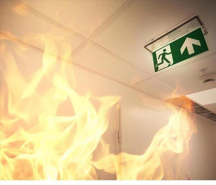 Fire burning and an exit sign on the ceiling.